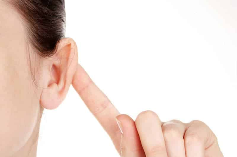 Fotografia de uma mulher segurando o ouvido