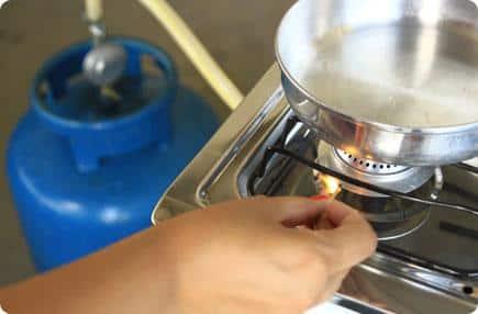 Pessoa acendendo um fogão usando um fósforo.