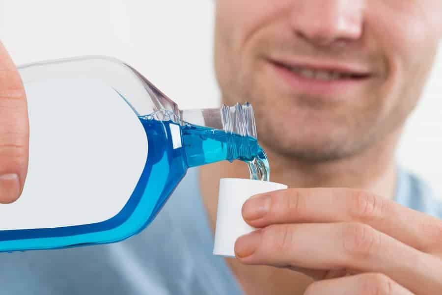 Man Pouring Bottle Of Mouthwash Into Cap