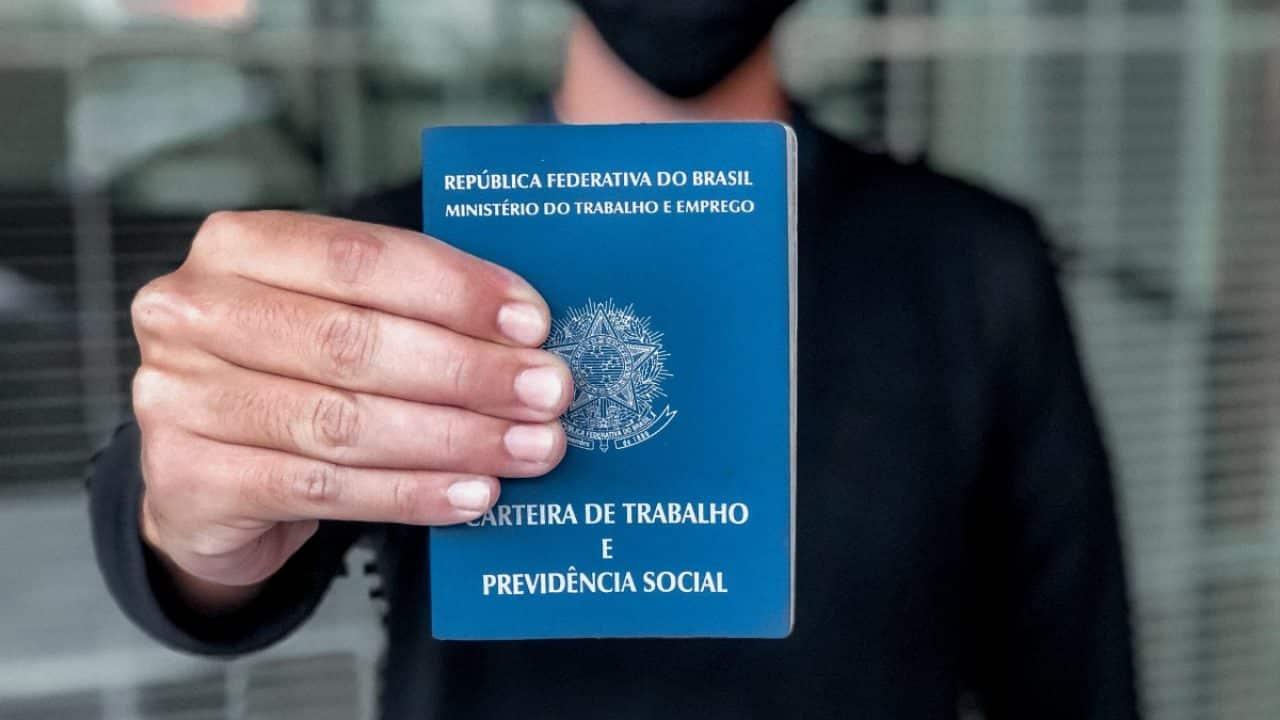 Fotografia de uma pessoa segurando a carteira de trabalho