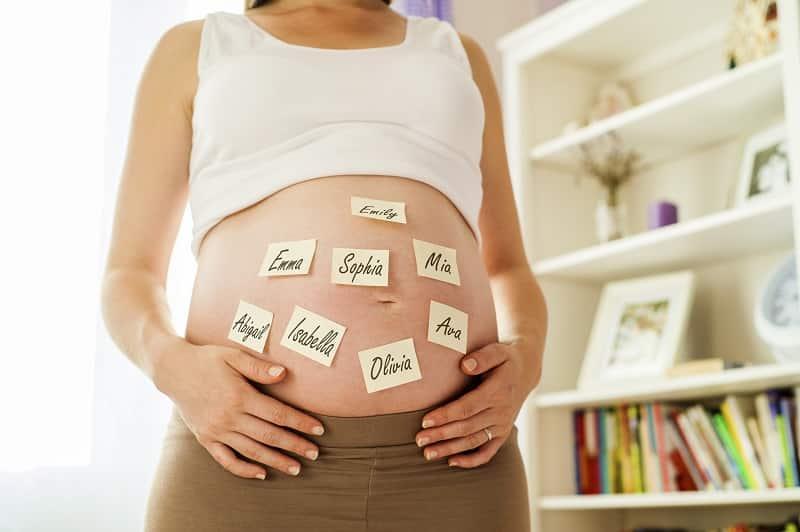 Fotografia de uma barriga de grávida com nomes grudados