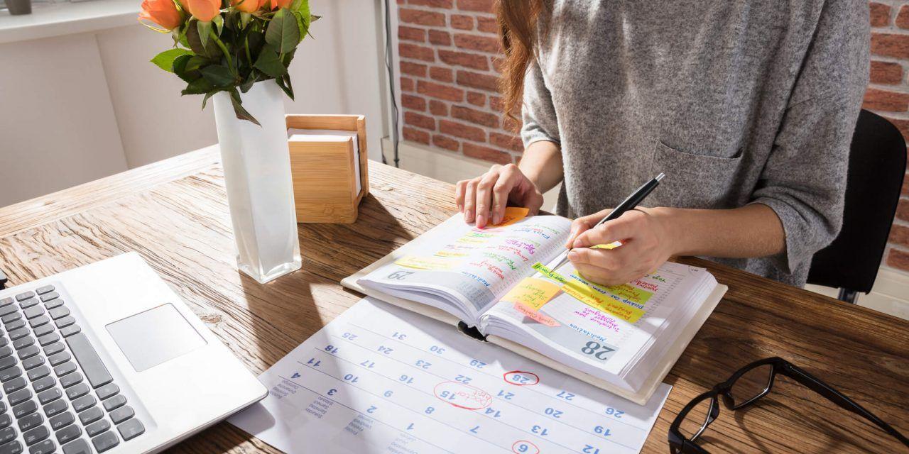 Fotografia de uma pessoa escrevendo na agenda para ilustração do item