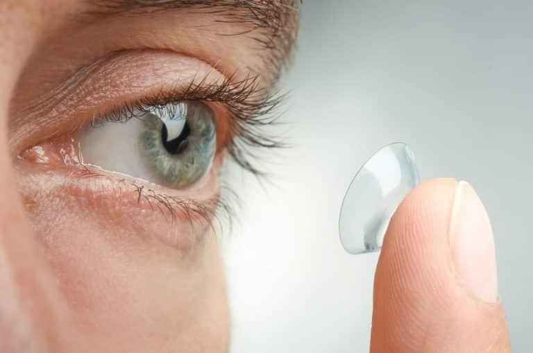 Fotografia de uma pessoa colocando lentes de contato para ilustração do item