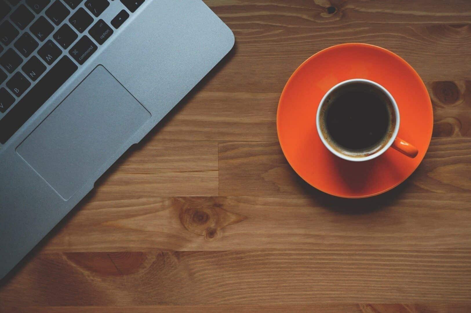 Fotografia de um café preto numa mesa com notebook para ilustração do item