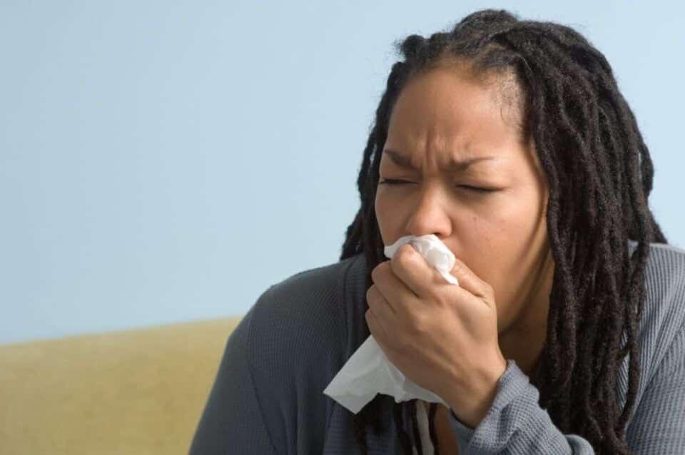 Fotografia de uma mulher tossindo para ilustração do item