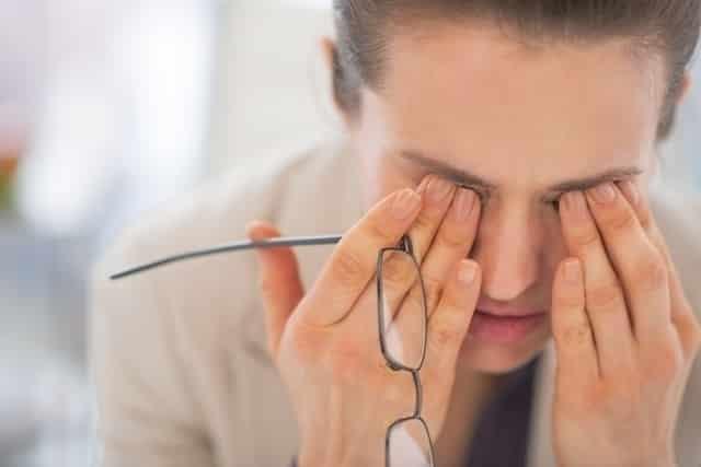 Fotografia de uma mulher com mãos nos olhos