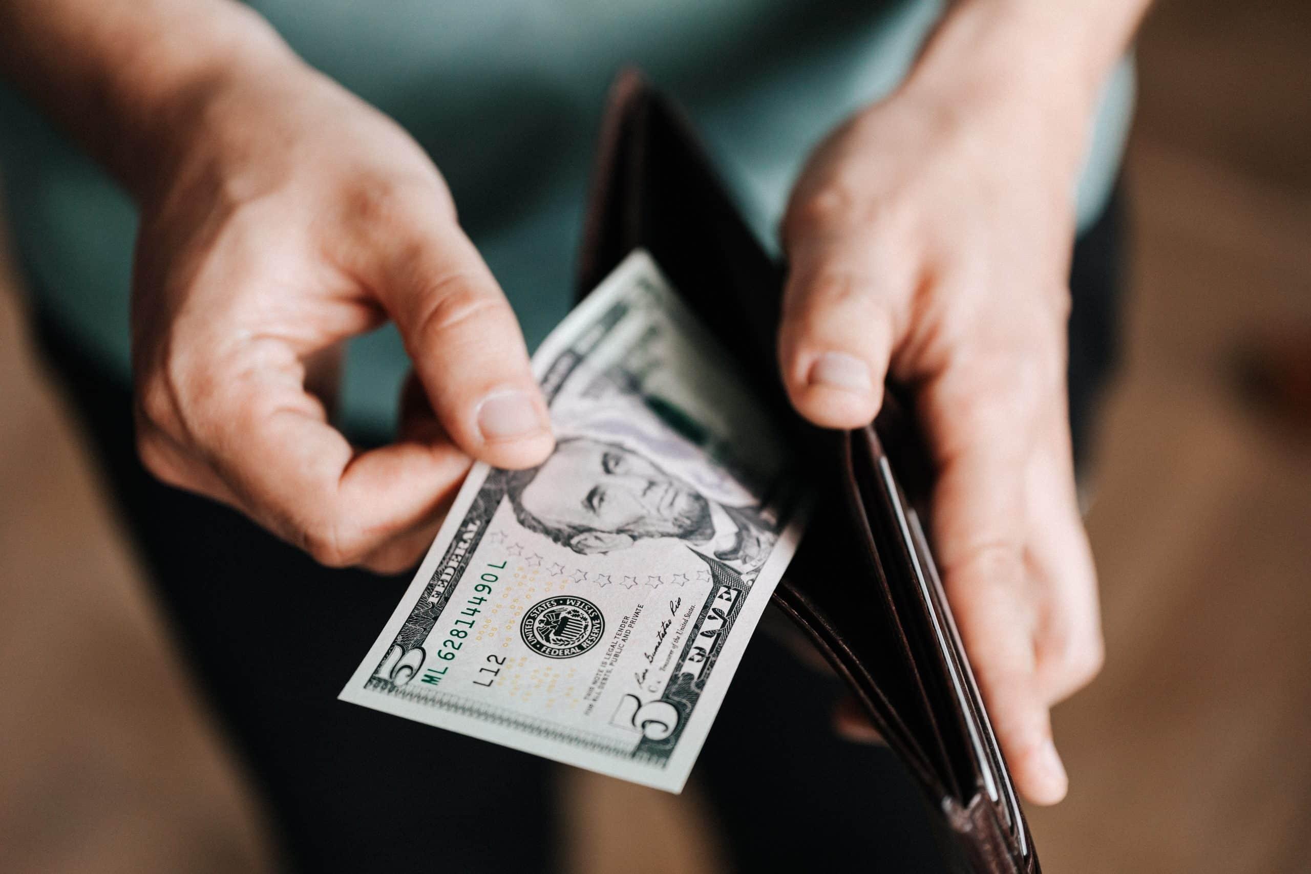 Fotografia de uma pessoa tirando dinheiro da carteira