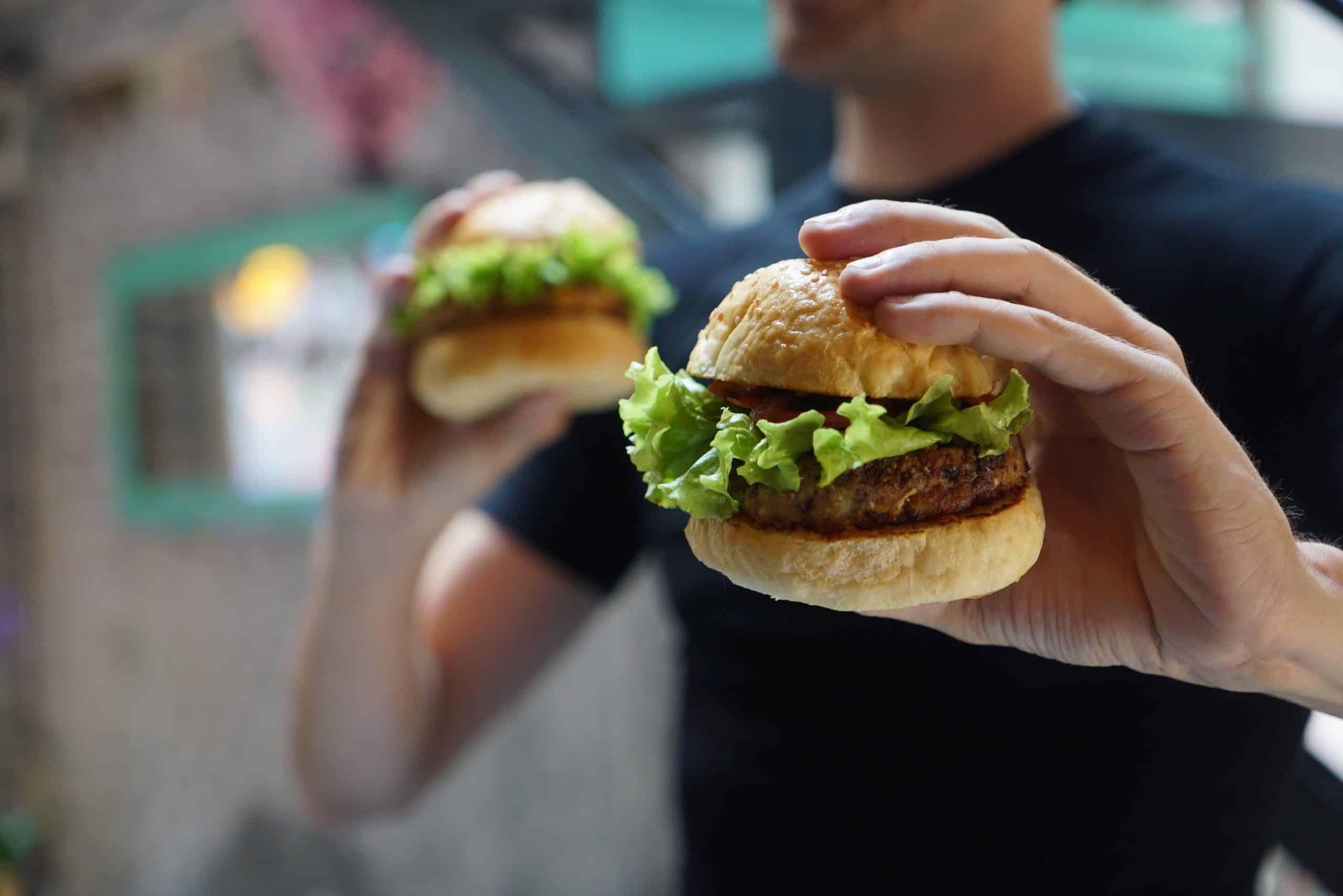 Fotografia de uma pessoa segurando dois sanduíches